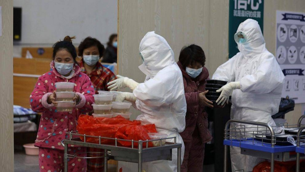 Nurses in protective suits distribute meals to patients at a temporary hospital at Tazihu Gymnasium in Wuhan in central China's Hubei province. — Courtesy photo