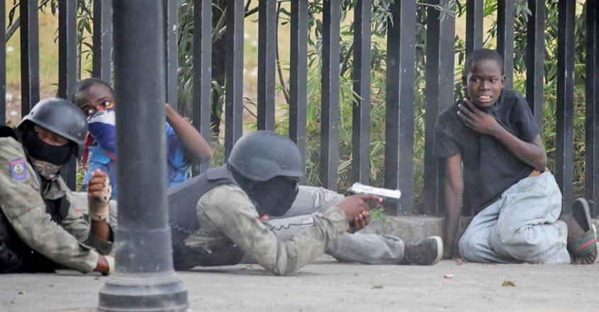 A boy gestures as a man in a Haitian National Police uniform aims a gun during a shooting in Champ de Mars, Port-au-Prince, Haiti, on Sunday. — Courtesy photo