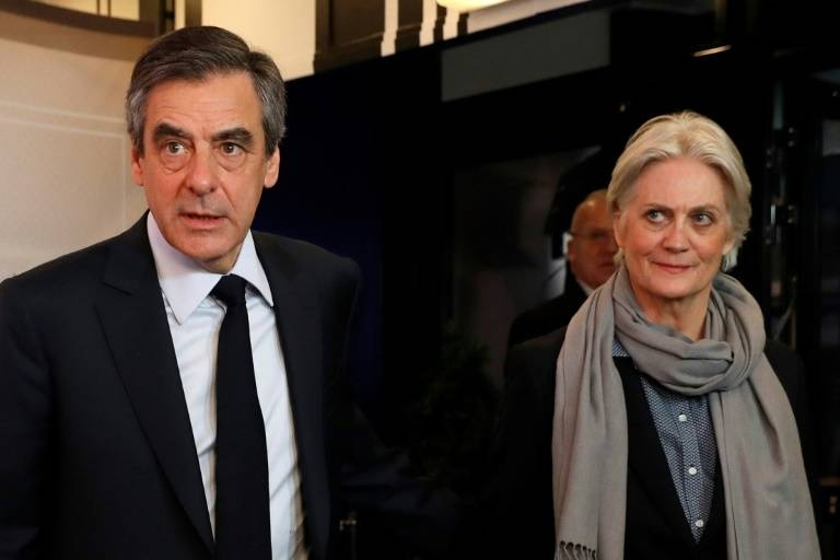 Former French Prime Minister Francois Fillon, left, and his wife, Penelope, face up to 10 years in prison over an alleged fake-jobs scandal. — AFP