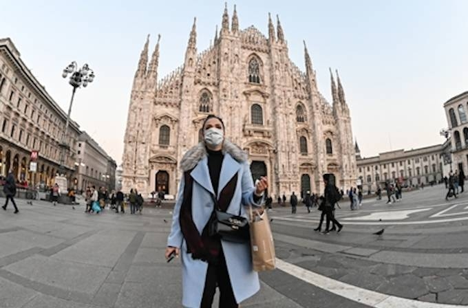 A woman with a protective facemask walks across the Piazza del Duomo, in front of the Duomo, in central Milan, on February 24, 2020, following security measures taken in northern Italy against the COVID-19 the novel coronavirus. — AFP