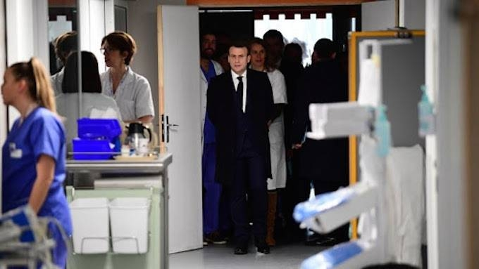 French President Emmanuel Macron (C) visits the Pitie-Salpetriere hospital in Paris on Thursday where the first French victim of COVID-19 passed away the day before. — AFP