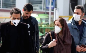 Iranians, with some wearing masks, wait to cross the street in Tehran in this Feb. 22, 2020, photo. — AFP