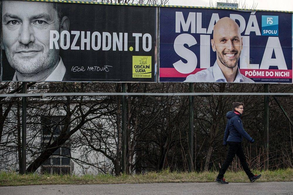 A woman walks past election posters of leader of the Ordinary People and Independent Personalities party, Igor Matovic (left), and leader of PS/Together party, Michal Truban, in Bratislava, Slovakia. – Courtesy photo