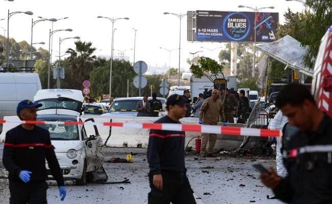 Police and firefighters gather at the scene of an explosion near the US embassy in the Tunisian capital Tunis on Friday. A blast that rocked Tunis today was an attack that targeted the US embassy and caused injuries among policemen, police said. — AFP
