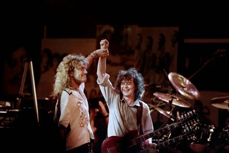 British singer Robert Plant, left, holds hands raised high with British guitarist Jimmy Page during a Led Zeppelin reunion performance at Madison Square Garden in 1988. — AFP