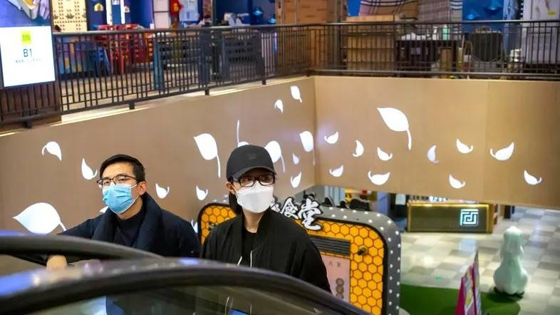 A couple wear face masks as they ride an escalator at a shopping mall in Beijing. — Courtesy photo