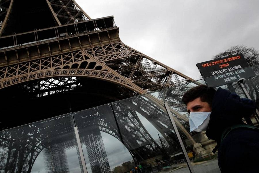 A man wearing a mask walks pasts the Eiffel tower closed after the French government banned all gatherings of over 100 people to limit the spread of the virus COVID-19, in Paris, on Saturday. — Courtesy photo