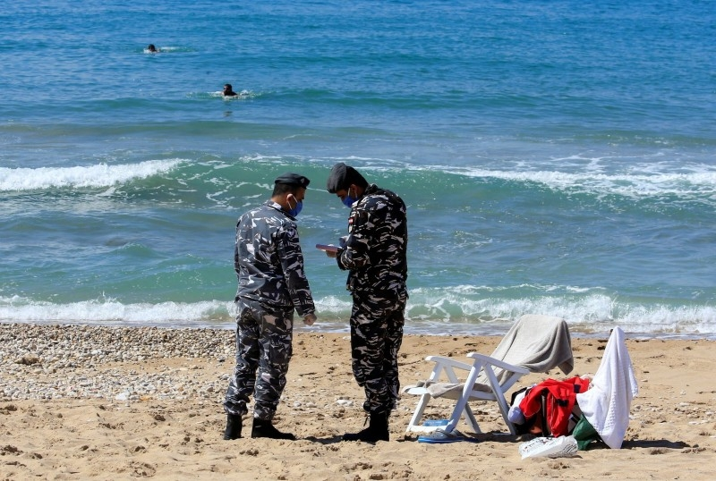 Lebanese officials issue fines at the beach in Sidon amid the nationwide lockdown.