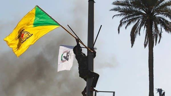A member of the PMU militias holds a flag of Kataib Hezbollah militia group during a protest in Baghdad to condemn airstrikes on their bases. -- Courtesy photo