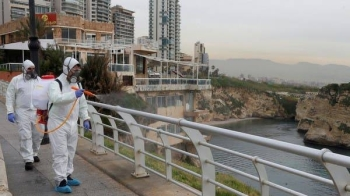 Employees from a disinfection company sanitize handrails as a precaution against the spread of the coronavirus at Beirut's seaside Corniche, Lebanon. -- Courtesy photo