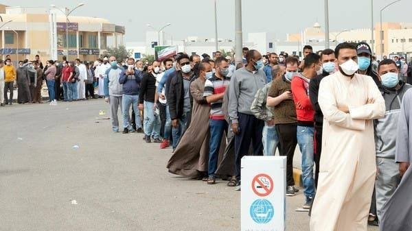 Expatriates wait in line to be tested at a makeshift center, following the outbreak of coronavirus, in Mishref, Kuwait, in this March 14, 2020 picture. — Courtesy photo