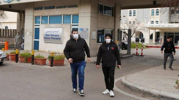 People wearing face masks walk outside Rafik Hariri hospital in Beirut, where Lebanon's first coronavirus case is being quarantined. -- File photo