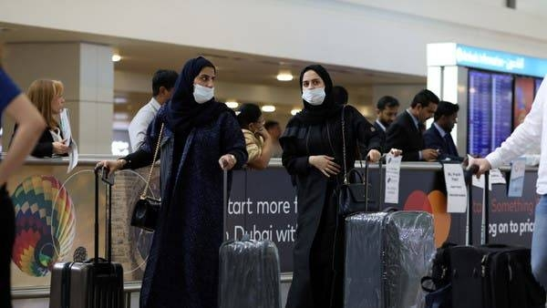 Travelers wear masks as they arrive at Dubai International Airport in this file photo