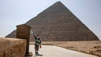 Municipal workers sanitize the areas surrounding the Giza Pyramids complex. -- File photo