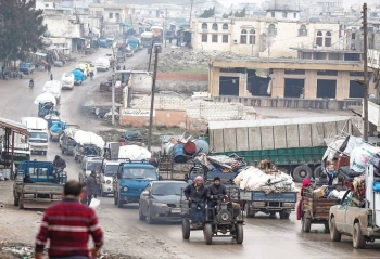 A convoy of trucks transporting Syrians and their belongings drives through the village of Al-Mastuma, in the northern countryside of Idlib province. -- Courtesy photo