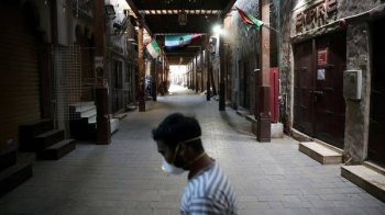 A man wearing a protective face mask walks through the deserted Barajeel Souq in old Dubai. -- File photo