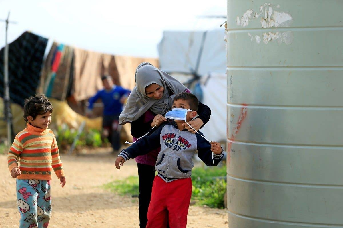 A Syrian refugee woman puts a face mask on a boy as a precaution against the spread of coronavirus, in Al-Wazzani area in southern Lebanon. -- File photo