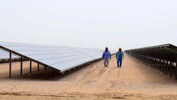 Employees walk past solar panels at the Mohammed Bin Rashid Al-Maktoum Solar Park near Dubai. -- File photo