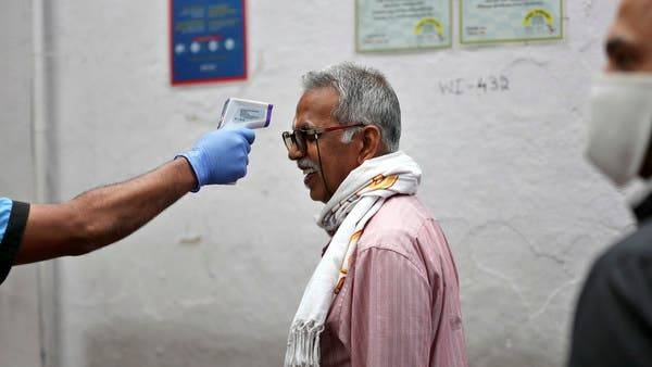 A staff member checks a man's body temperature before allowing him into an eatery in the southern Indian city of Bengaluru. -- Courtesy photo