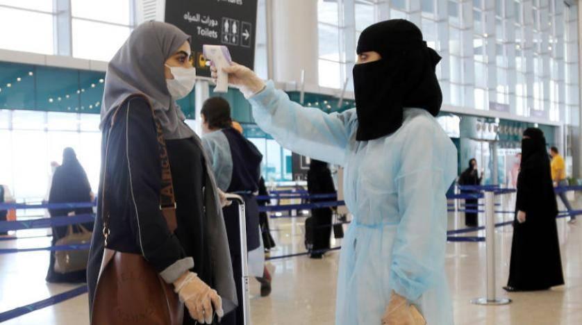 A security woman checks the temperature of a woman at Riyadh's King Khalid International Airport on Sunday. — Courtesy photo