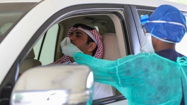A health worker, wearing personal protective equipment, collects a swab sample from a man at a drive-thru testing service for COVID-19 coronavirus in the Qatari capital Doha. -- Courtesy photo