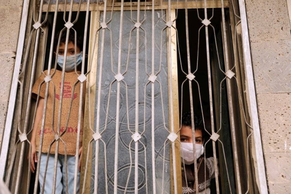 Children wearing protective masks look from behind a window during a 24-hour curfew amid concerns about the spread of the coronavirus disease (COVID-19), in Sanaa. — Courtesy photo