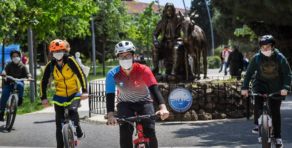 Young men wear face masks while cycling in a park in Büyükçekmece, Turkey. UNDP/Levent Kulu.