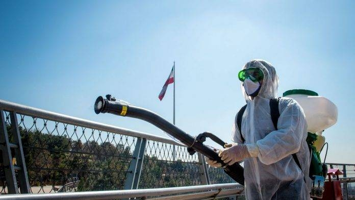 A firefighter in protective clothing, mask and goggles, sprays disinfectant on Tabia't bridge pedestrian overpass in Tehran, Iran. -- File photo
