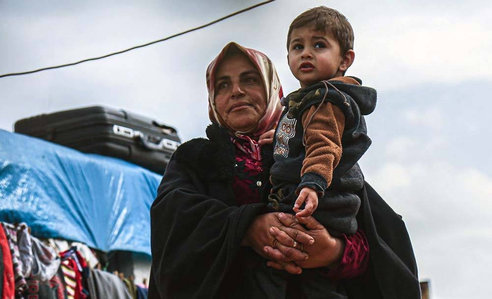 A widow holds her grandson in a displaced persons camp in northern Idlib Governorate, Syria. — courtesy OCHA/Steve Hafez