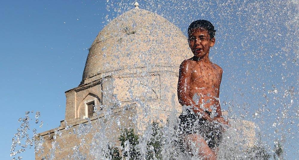 An 11-year-old boy finds relief from the summer heat by playing in a fountain in a historic part of the city of Samarkand, Uzbekistan. — courtesy UNICEF/Pirozzi