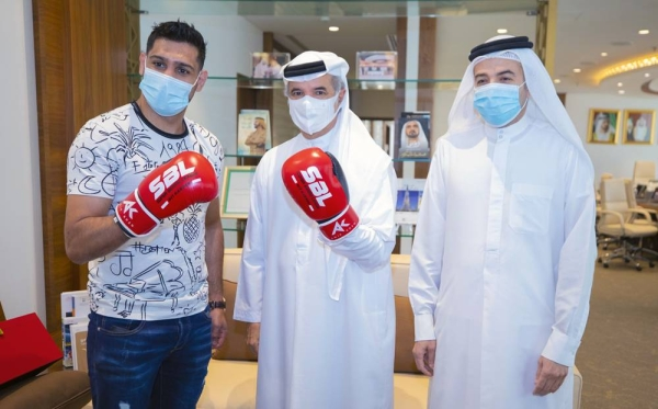 Two-time world champion Amir Khan with Saeed Hareb, secretary general of DSC, and Nasser Aman Al Rahma, assistant secretary general of DSC.