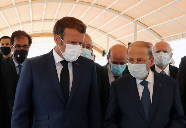 French President Emmanuel Macron, left, walks with Lebanese President Michel Aoun at Rafic Hariri International Airport in Beirut on Thursday. — Courtesy photo