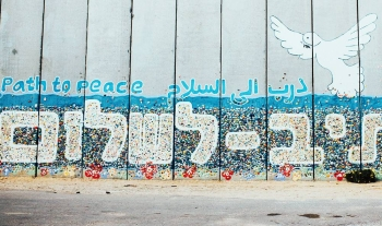 A mural on a wall in Netiv HaAsara, Israel, that faces the Gaza border and reads Path to Peace in Hebrew, Arabic, and English. — courtesy Unsplash/Cole Keister