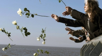 Visitors throw white flowers into Rio de la Plata in Buenos Aires out of respect and remembrance for the tens of thousands of people who disappeared during Argentina's so-called