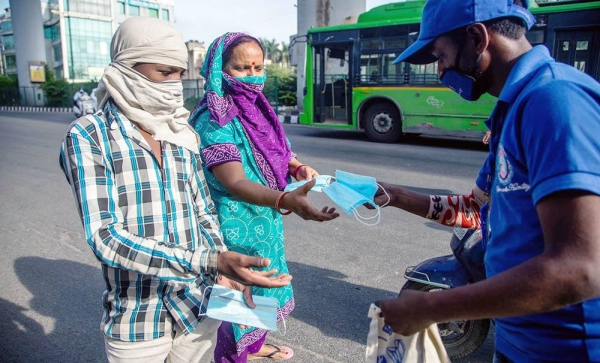 A volunteer distributes free masks to Indians in New Delhi. As part of fundamental and lasting changes in social behavior being ushered in by the coronavirus, COVID-19, pandemic, 107 cities in India are to have pop-up cycle lanes, traffic-calmed sections and non-motorized zones.