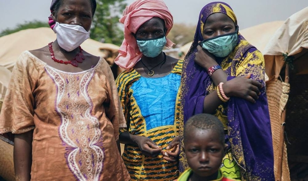 In Niger attacks by armed groups have been on the rise, exacerbating the plight of communities reeling under the impact of the pandemic. Pictured here, a woman with members of her family, who were forced to flee their homes due to violence and insecurity. — courtesy UNICEF/Juan Haro