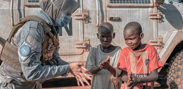 A peacekeeper with MINUSCA, the UN mission in the Central African Republic, explains to two young boys how to properly apply hand sanitizer as protection against coronavirus. — courtesy MINUSCA/Indonesia FPU
