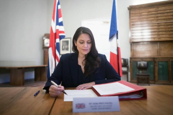 British Home Secretary Priti Patel seen signing an agreement on Saturday to beef up police presence in the English Channel with her French counterpart Gerald Darmanin.