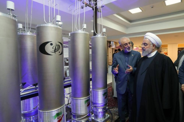 File photo of Iranian President Hassan Rouhani seen at an exhibition of Iranian nuclear technologies, standing next to model centrifuges used to refine uranium and other nuclear materials.