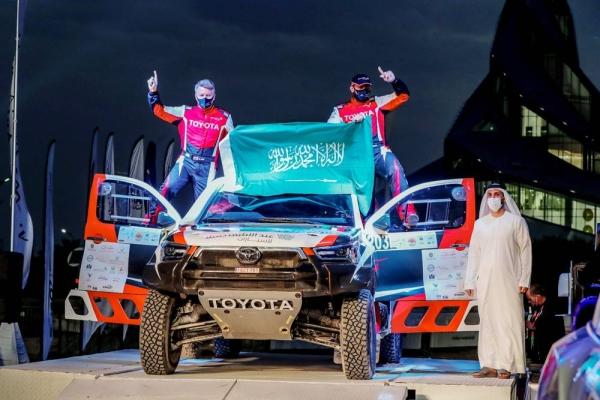 Saudi Arabia's Yazeed Al Rajhi and co-driver Michael Orr, with Emirates Motorsports Organization CEO Mahir Badri.