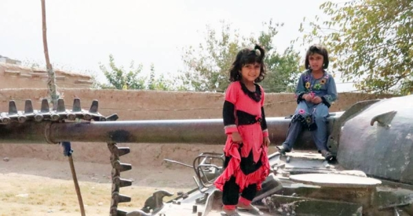 Children in Kandahar play on a destroyed tank, a relic of a past war with the then Soviet Union. — courtesy UNAMA Photo/Mujeeb Rahman Hotaki