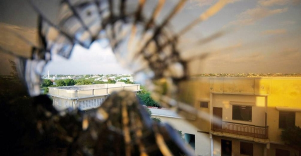 The skyline beyond the northern suburbs of Mogadishu is seen through a bullet hole in the window of a hotel in Somalia. — courtesy UN Photo/Stuart Price