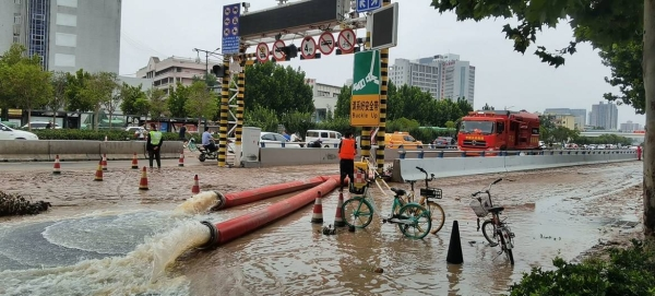 Rescuers pull villagers from flood waters in Xingyang city in China's Henan Province. — Courtesy photos