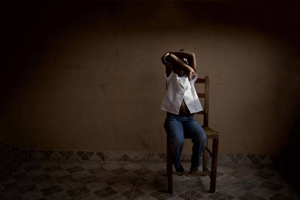 An eight-year-old girl hides her face at a UNICEF-supported center in Haiti that provides temporary care and support for trafficked children while authorities search for their parents in this courtesy file photo.
