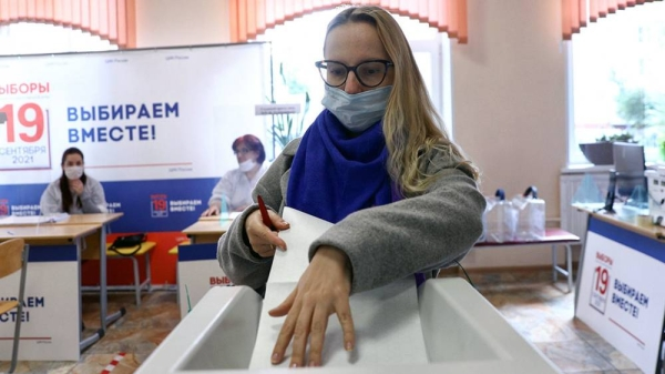 A Russian voter is seen casting her ballot. Millions of Russians cast their vote this weekend in a general election expected to bring little political change.