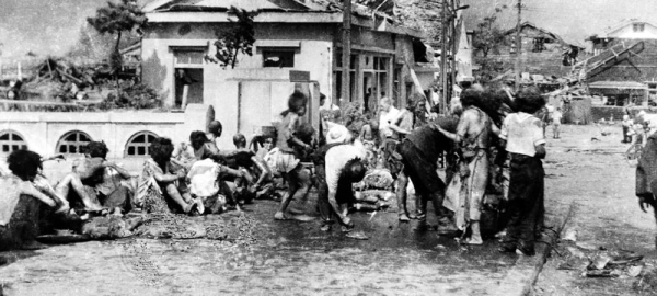 Injured civilians, having escaped the raging inferno, gathered on a pavement west of Miyuki-bashi in Hiroshima, Japan, at about 11 a.m. on Aug. 6 1945. — courtesy UN Photo/Yoshito Matsushige
