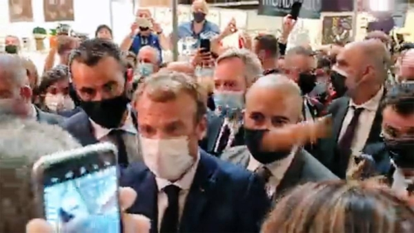 A videograb shows French President Emmanuel Macron unaware of the 'egg' missile being thrown at him during his visit to a restaurant trade fair in Lyon. The egg bounced off Macron's shoulder without breaking.