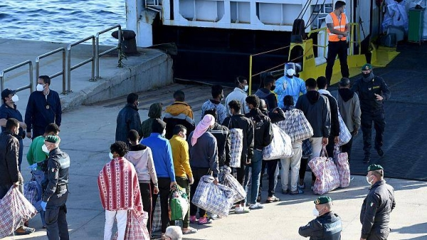 In this file photo from May 2021, migrants are seen before boarding a ship on being transferred from the migrant center on Lampedusa island.